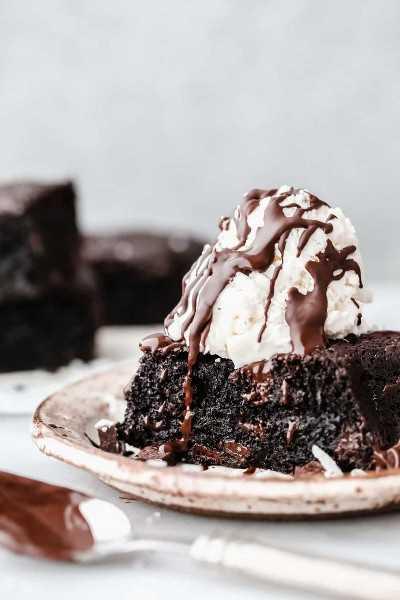Keto brownie ganó un plato con una cucharada de vainilla sobre la parte superior y roció con dulce de chocolate.