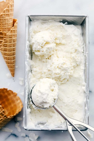 Helado de keto en una sartén del congelador con una bola de helado sacada y conos de waffle al lado.