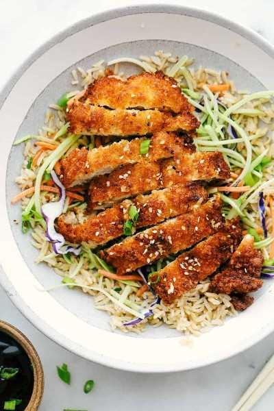 Pollo Katsu picado en rodajas y agregado sobre el repollo y el arroz.