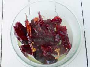 Remoje los pimientos en agua hirviendo para ablandarlos y rehidratarlos.