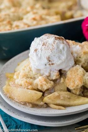 Zapatero de manzana cubierto con helado en un plato blanco con un plato de zapatero de manzana en el fondo