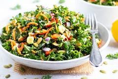 Uma receita saudável para salada de couve com cenoura, abacate e molho de salada de limão em uma tigela branca.