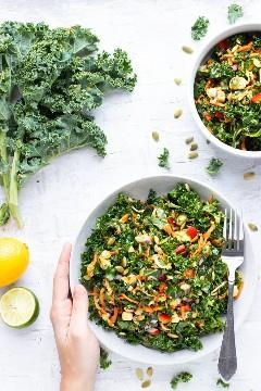 Duas tigelas de salada cheias de uma receita saudável de salada de couve com molho de abacate e limão.