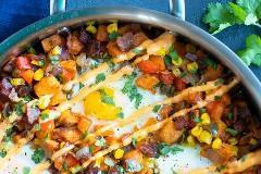 Una sartén de acero inoxidable llena de papas fritas con huevo y sriracha mayo.