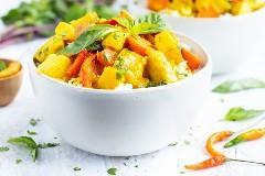 Un tazón blanco para servir de curry tailandés que se hace con pasta de curry amarillo, pollo, papas y zanahorias.