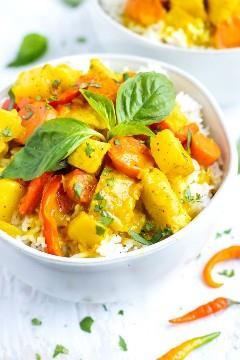 Un tazón grande para servir lleno de receta de curry amarillo tailandés con pollo y papas.