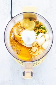 Un procesador de alimentos lleno de ingredientes para una receta de pasta de curry amarillo tailandés.