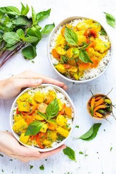 Dos tazones llenos de una receta de curry de coco con chiles tailandeses al lado.