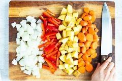 Cebolla, pimiento rojo, papas Yukon Gold y zanahorias como ingredientes en una receta de pollo al curry amarillo.
