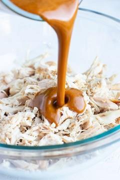 Molho de manteiga de amendoim asiático é derramado em uma tigela clara cheia de frango assado ralado.