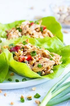 Alface de frango é embrulhada em folhas de alface Bibb em um prato branco ao lado de cebolinha.
