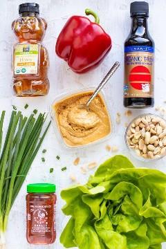 Uma garrafa de mel, pimenta vermelha, molho de soja sem glúten, manteiga de amendoim macia, molho Sriracha, amendoim torrado e alface Bibb em uma mesa branca como ingredientes para um envoltório de alface asiático.