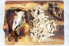 Um frango assado que foi moído em uma tábua de madeira para uma receita de alface.