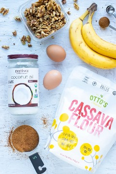 El aceite de coco, el azúcar de coco, la harina de yuca, los plátanos maduros, las nueces y la canela en una mesa blanca como ingredientes de una receta de panecillos de nuez de plátano.