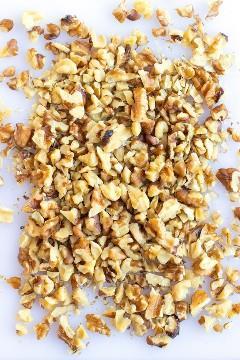 Una tabla de cortar blanca con nueces picadas para la mejor receta de magdalenas de plátano.