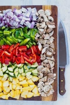 Una tabla para cortar llena de calabacín amarillo, calabacín, cebolla roja, pimiento verde y rojo y champiñones.