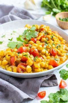 Una receta de curry de garbanzos saludable y fácil servida en un tazón blanco sobre una mesa blanca.