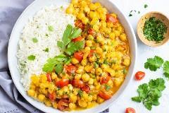 Curry del garbanzo vegano en un cuenco blanco con el arroz basmati al lado del cilantro.
