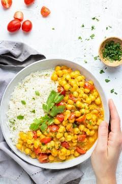 Una mano que sostiene un tazón lleno de curry indio vegano con un tazón pequeño de cilantro al lado.