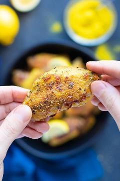 As mãos pegando uma pimenta de limão frango fin de uma tigela de limão pimenta asas.