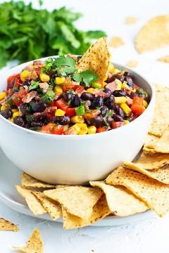 Receta de salsa de frijoles negros con maíz, cebolla verde y salsa en un tazón blanco con chips de tortilla de maíz.