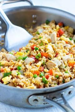 Una sartén llena de una receta rápida y fácil de arroz frito con una espátula de metal.