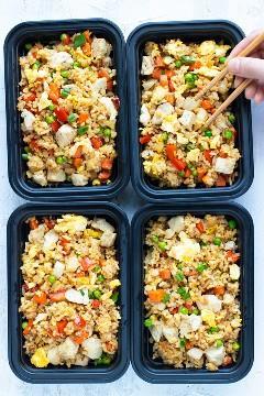 Recipientes de preparação de alimentos cheios de arroz frito com frango e uma mão pegando alguns com pauzinhos.