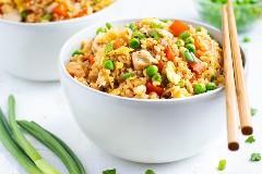 Uma tigela branca cheia de uma receita saudável de arroz frito com cenouras e ervilhas ao lado de cebolinha.