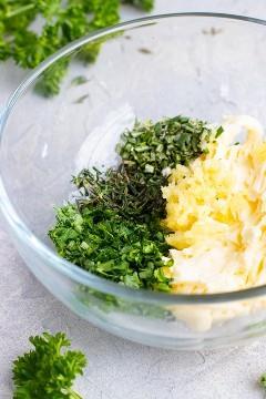 Un tazón claro lleno de mantequilla, ajo y hierbas.