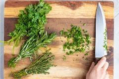 Rosemary, tomillo y perejil en una tabla de cortar de madera con un cuchillo.
