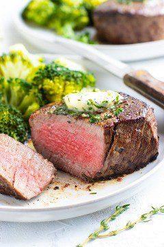 Un filete mignon que se ha cocinado a medio-raro en un plato blanco con un cuchillo y brócoli.
