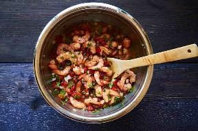 Preparación de ceviche de camarón con una cuchara de madera en un tazón de fuente de mezcla de acero inoxidable