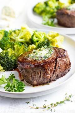 La mejor receta de filet mignon en un plato blanco con brócoli.