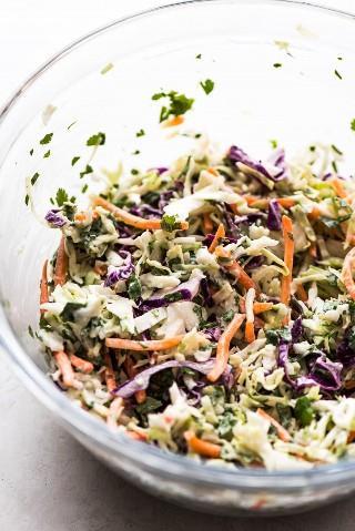 Una cremosa ensalada de repollo hecha con repollo verde y rojo, zanahorias y cilantro cubiertos de mayonesa y jugo de limón para una receta de Baja Fish Tacos.