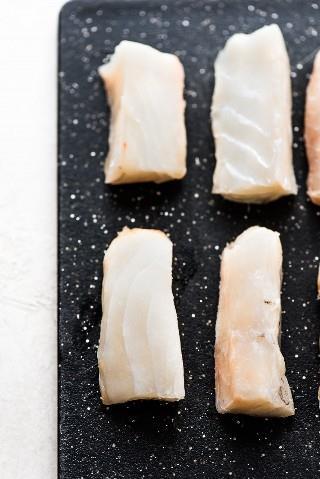 Rebanadas de Atlantic Cod en una tabla de cortar negra para la receta de Baja Fish Tacos.