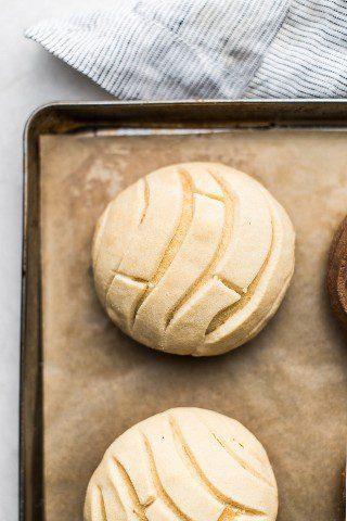 Un pan de concha de vainilla con costra de vainilla, ligero y aireado, en una bandeja para hornear.