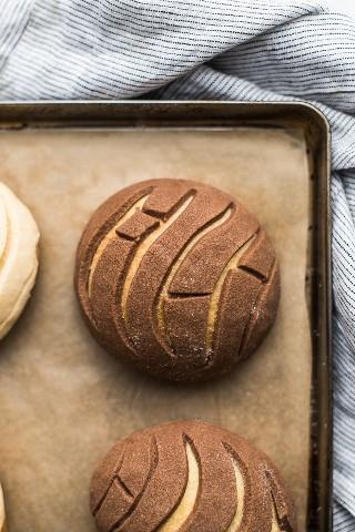 Un ligero y amplio pan de concha con costra de chocolate en una bandeja para hornear.