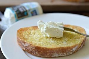 añadiendo queso de cabra a la bruschetta