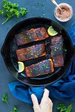 Receta de salmón ennegrecido en una sartén de hierro fundido negro con un cuenco lleno de condimento ennegrecido al lado.