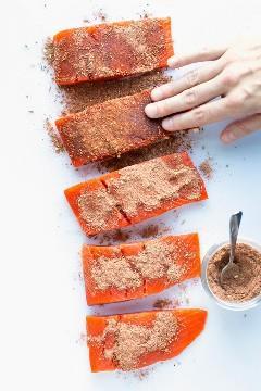 Mezcla de condimento ennegrecido que se frota en filetes de salmón en una tabla de cortar blanca.