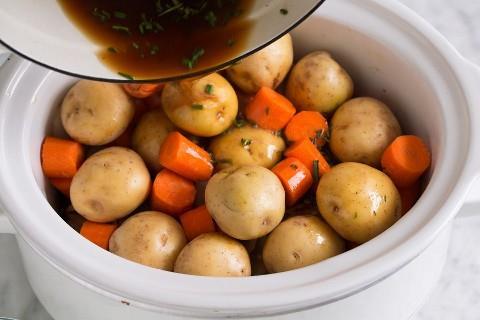 Agregue las papas y las zanahorias sobre el asado de chuck y vierta sobre la mezcla de caldo de res.