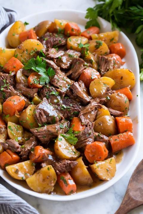Pote asado de la olla de cocción lenta con papas y zanahorias en una fuente blanca adornada con perejil.