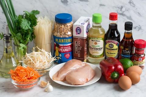 Los ingredientes necesarios para el pad thai que se muestra aquí incluyen huevos, hojuelas de pimiento rojo, salsa de pescado, salsa de soja, vinagre de arroz, lima, pimiento, pollo, azúcar moreno, cacahuetes, fideos de arroz, cilantro, cebollas verdes, brotes de soja, zanahorias, ajo y aceite vegetal.