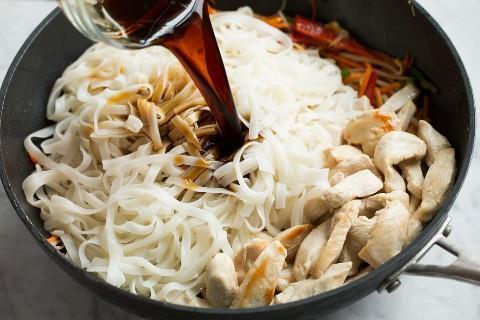 Agregar fideos de arroz, pollo cocido y salsa para terminar Pad Thai en wok.