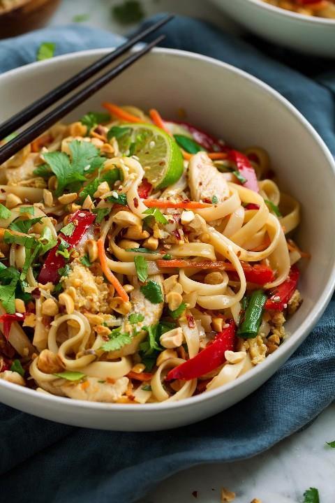 De cerca la imagen de Pad Thai mostrando fideos de arroz, verduras, pollo, maní y cilantro.