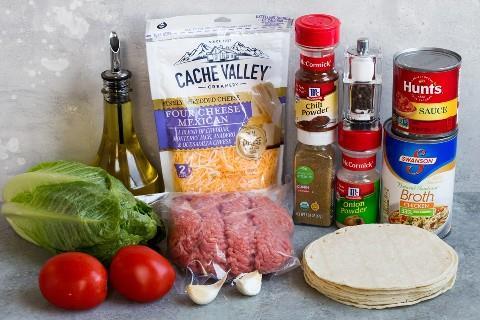 Os ingredientes necessários para fazer as tacos mostradas aqui incluem carne picada, óleo, temperos, molho de tomate, caldo de carne, tortilhas, queijo, alface, tomate com alho.