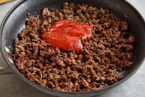 Adicione o molho de tomate e o caldo de frango à carne de taco e encha a frigideira.