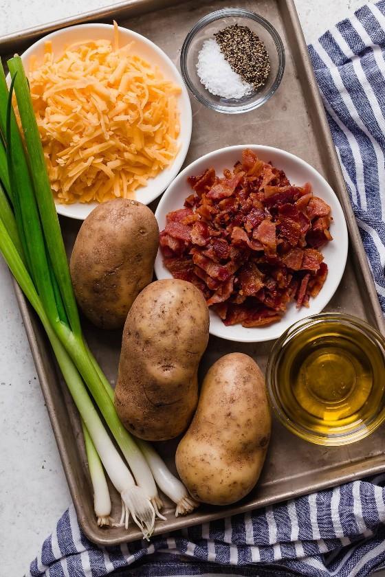 Os ingredientes necessários para fazer as batatas com queijo mostradas aqui incluem batatas, bacon, queijo cheddar, azeite, condimentos.