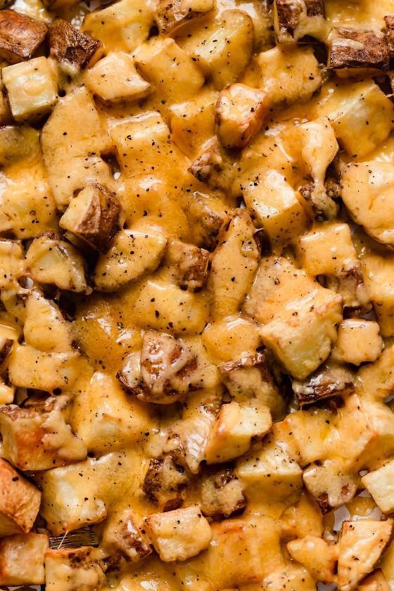 Cubos de batata assada com queijo cheddar derretido.