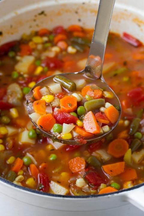 Cucharón lleno de sopa de verduras casera saludable.